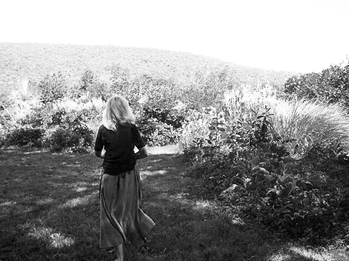 photo-carol walking into Flower Hill Farm Retreat garden B&W19
